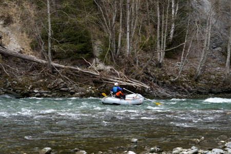 Man rafting with his dog in a rubber boat on river Rhine in Safiental, Switzerland on early spring.
