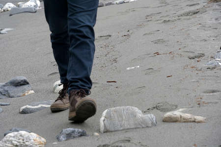 Man walking on sandy beach. He is wearing boots. Only his legs are visible. He is approaching the camera. There is a lot of copy space.