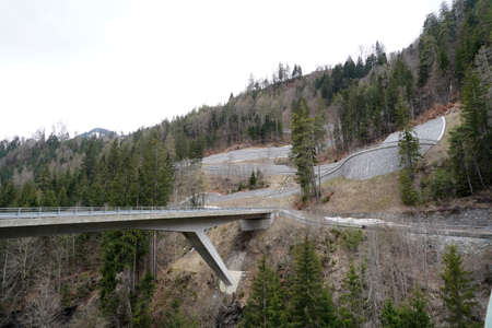 Serpentine road on a mountain slope in region Versam in Switzerland. There is as well a bridge over local river Rabiusa.