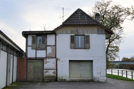 Old abandoned house on the bank of river Aare in Aarburg, Switzerland. There is an analogue aerial on the roof.