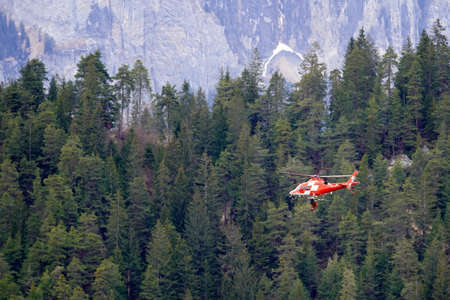 Versam, Switzerland, 04 10 2021, Helicopter of Swiss rescue system flying over Ruinaulta ravine or gorge, performing a rescue action. On the background there is coniferous woodland and rocky wall.