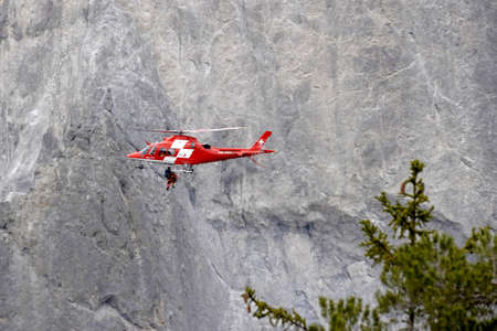 Versam, Switzerland, 04 10 2021, Helicopter of Swiss rescue system flying over Ruinaulta ravine or gorge, performing a rescue action. On the background there is a rocky wall.