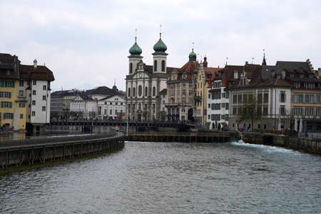 Lucerne, Switzerland 04 17 2021: Waterfront of Lucerne, old city along the river Reuss, with dominant Jesuit church and Reuss Bridge in the foreground.