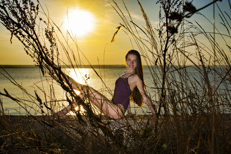 Ballerina resting on lake shore at sunset