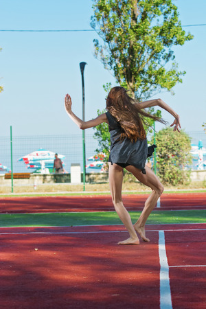 Ballerina dancing on tennis court