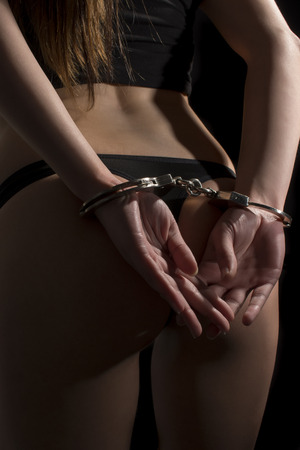handcuffs: Hand cuffed woman isolated on  black background