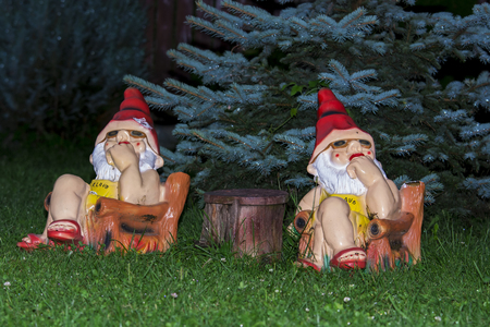 Garden gnomes watching and thinking at table in garden Stock Photo