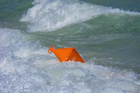 Orange buoy crushed on beach by  waves