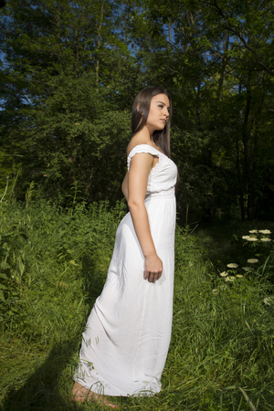 Young girl posing in grass field wearing white dress