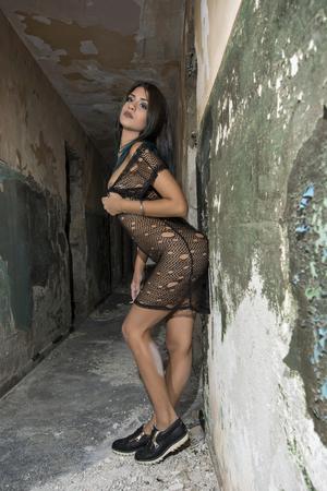 light blue lingerie: Young girl posing in a black fishnet dress Stock Photo