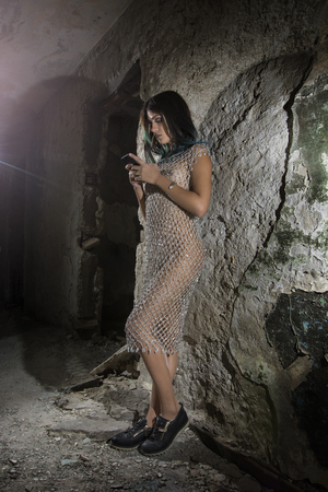 Young girl posing in a silver fishnet dress Stock Photo