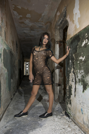 Young girl posing in a black fishnet dress Stock Photo
