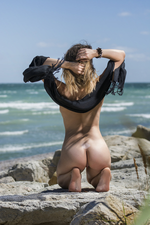 Beautiful young sexy nude woman enjoying nature by the sea.