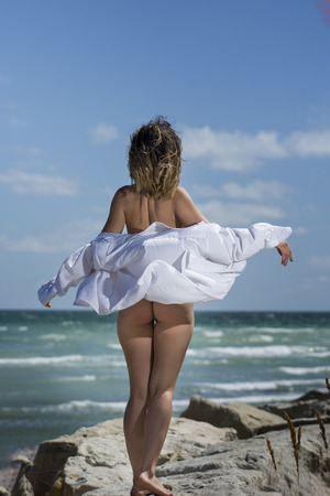 Beautiful young sexy nude woman enjoying nature by the sea