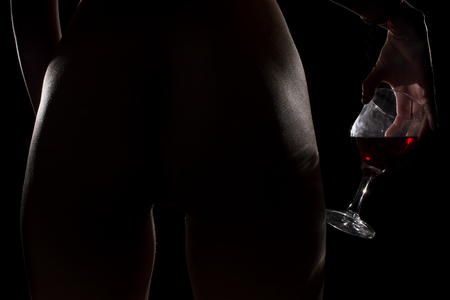 Silhouette of a body part , nude woman with glass or wine on black background