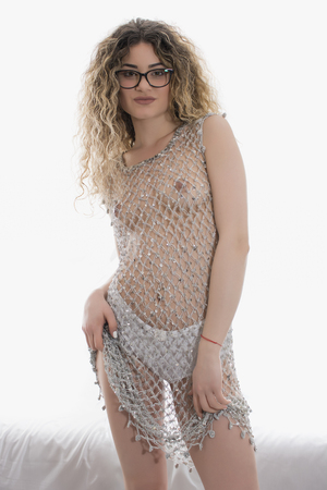 Young  girl with curly hair posing in a silver fishnet dress on white background