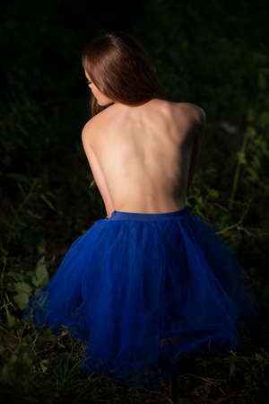Young girl posing in a blue dress on forest background
