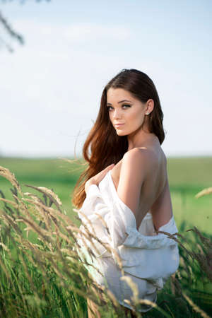 Beautiful young woman posing in a grass field Banque d'images