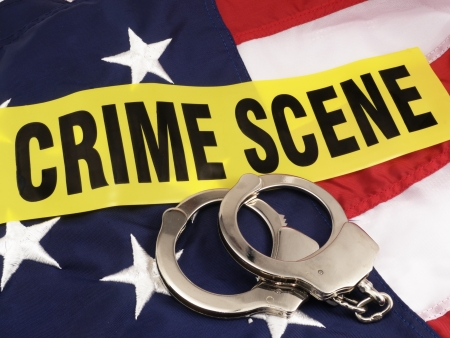 News Concept  Hand Cuffs And Crime Scene Cordon Tape Over American Flag - Suggests Crime In American And Police Response