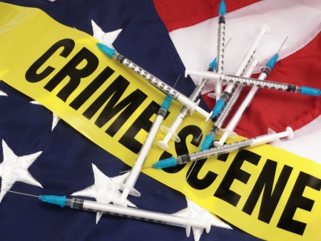 News Concept  Drug Syringes And Crime Scene Cordon Tape Over American Flag - Suggests Drug Crime In America