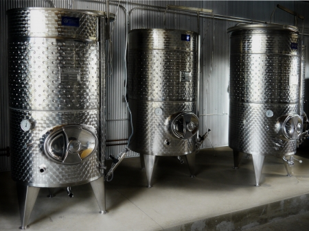 winemaking: Three stainless steel wine fermenters in a modern winery Stock Photo