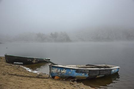 frozen lake: Two wooden boats at frozen lake, wintertime, foggy weather