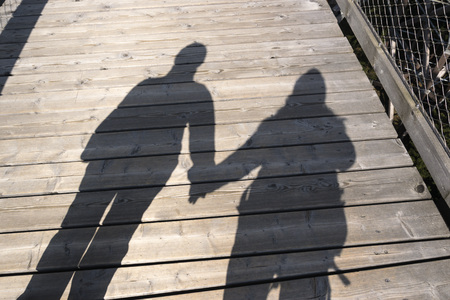 silhouette of two people holding their hands in sunlight, a couple of hikers walking a wood path   Stockfoto
