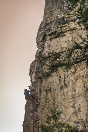 A climber climbing a sandstone rock during sunset
