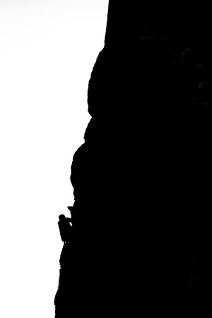 silhouette of a climber climbing a rocky mountain, black and white image,  Stockfoto