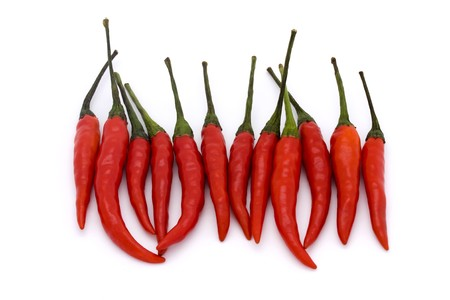 tapering: line of birds eye  chillies on a white background