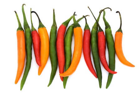 tapering: mixed coloured chilli peppers on a white background