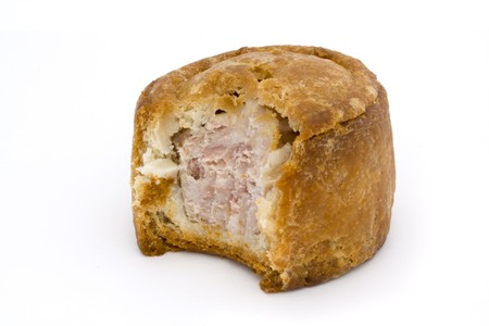 small pork pie with bite taken on a white background