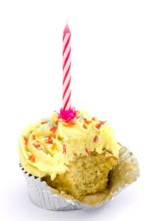 yellow cupcake with candle and bite taken over white