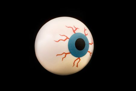 dilated pupils: rubber toy eyeball isolated on a black background