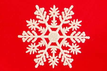 single white snowflake isolated over red