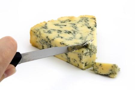 calorific: Blue cheese being cut isolated on white