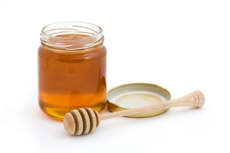 Jar of open honey with drizzler over white