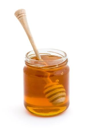 Honey dripper in a jar of honey over white