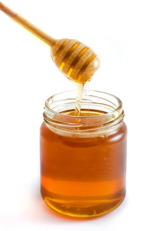 honey jar: Honey dripping into jar isolated over white