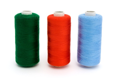 Three rolls of different colour cotton isolated on white