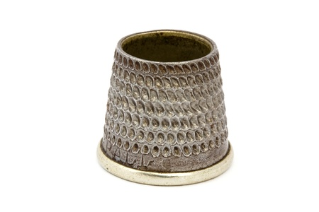 Close up of an old silver thimble over white Stock Photo