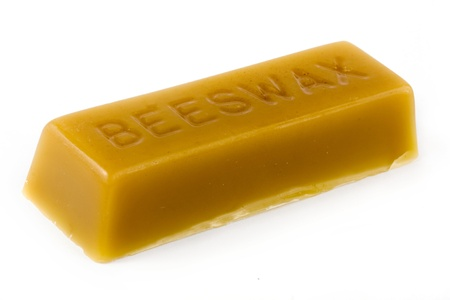 Stick of beeswax over white