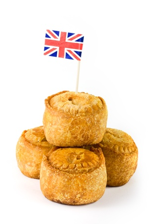 Pile of pork pies with union jack flag on white photo