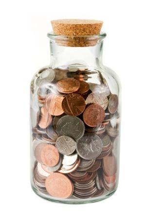 sterlina: Bottiglia di vetro piena di monete su bianco Archivio Fotografico