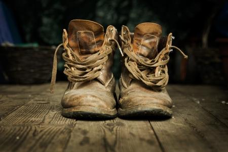 botas: Par de viejas botas desgastadas en tarimas de madera