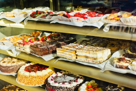 Window of a cake shop with a variety of cakes on display photo