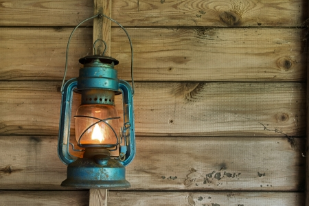 Rusty lit blue lantern hanging in an old shed photo