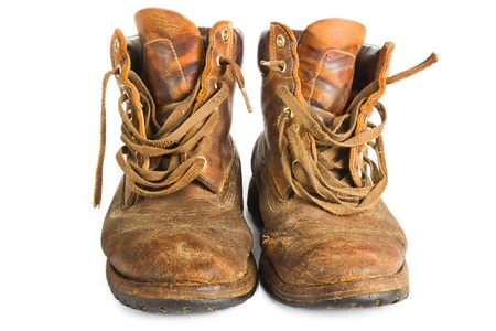 Pair of old worn brown leather work boots on white Stock Photo
