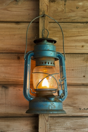 Rusty lit blue lantern hanging in an old shed Stock Photo - 15027475