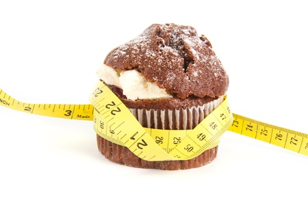 Chocolate muffin with a tape measure around it over white